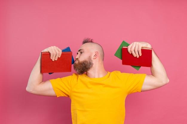 Dorosły muskularny facet na co dzień z brodą całuje ulubione książki na różowym tle