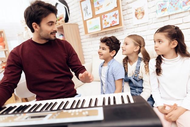 Dorosły nauczyciel, który gra na pianinie.