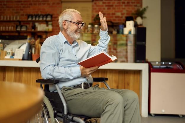 Dorosły niepełnosprawny mężczyzna na wózku inwalidzkim czytający książkę