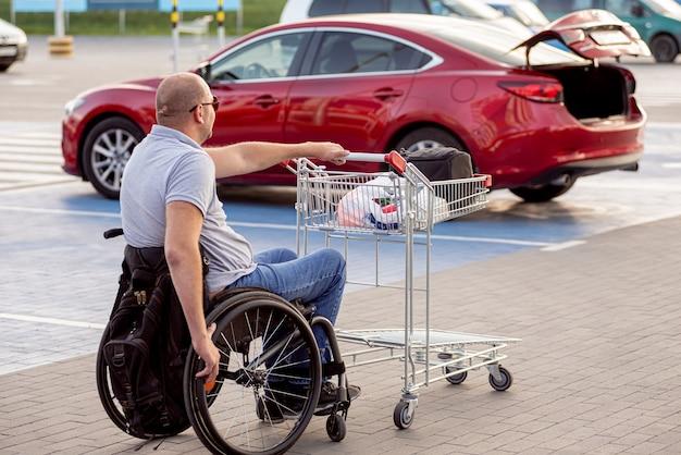 Dorosły niepełnosprawny mężczyzna na wózku inwalidzkim pcha wózek w kierunku samochodu na parkingu supermarketu