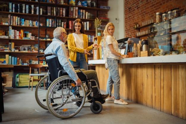 Dorosły niepełnosprawny mężczyzna na wózku inwalidzkim w kolejce po kawę, niepełnosprawność, wnętrze kawiarni na tle. niepełnosprawny starszy mężczyzna, sparaliżowani ludzie w miejscach publicznych