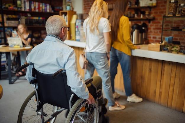 Dorosły niepełnosprawny mężczyzna na wózku inwalidzkim w kolejce w kawiarni, niepełnosprawność, wnętrze kawiarni na tle. niepełnosprawny starszy mężczyzna, sparaliżowani ludzie w miejscach publicznych