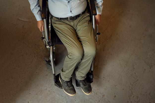 Dorosły niepełnosprawny mężczyzna na wózku inwalidzkim, widok z góry, betonowa podłoga na tle, niepełnosprawność. niepełnosprawny starszy mężczyzna, sparaliżowani starsi ludzie