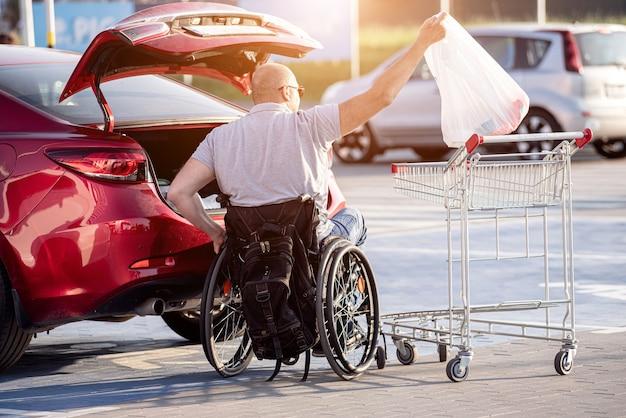 Dorosły niepełnosprawny mężczyzna na wózku inwalidzkim wkłada zakupy do bagażnika samochodu na parkingu supermarketu