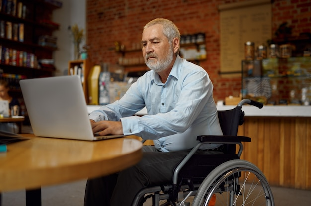 Dorosły niepełnosprawny mężczyzna na wózku inwalidzkim za pomocą laptopa, niepełnosprawności, regału i wnętrza biblioteki uniwersyteckiej na tle. niepełnosprawny starszy mężczyzna, osoby sparaliżowane zdobywają wiedzę