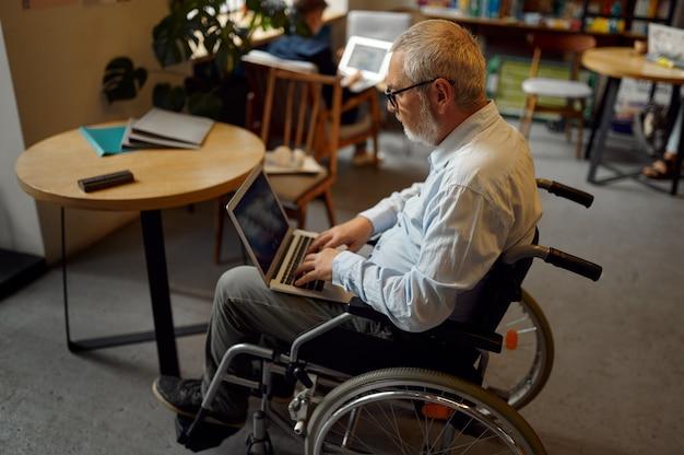 Dorosły niepełnosprawny mężczyzna na wózku inwalidzkim za pomocą laptopa, widok z góry, niepełnosprawność, półka na książki i wnętrze biblioteki uniwersyteckiej na tle. niepełnosprawny starszy mężczyzna, osoby sparaliżowane zdobywają wiedzę