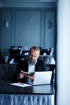 Dorosły odnoszący sukcesy mężczyzna biznesmen pracuje nad nowym projektem i patrzy na wykresy wzrostu w zeszycie. siedzi przy stole i pracuje. patrzy na notatnik i uśmiecha się