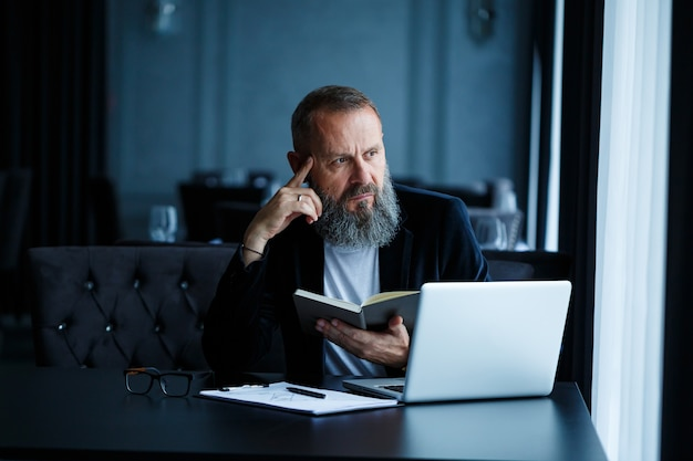 Dorosły, odnoszący sukcesy mężczyzna biznesmen pracuje nad nowym projektem i patrzy na wykresy wzrostu w zeszycie. siedzi przy stole przy dużym oknie. patrzy na notatnik i uśmiecha się
