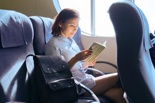 Dorosły pasażer płci żeńskiej siedzi na fotelu w pobliżu okna w kabinie promu