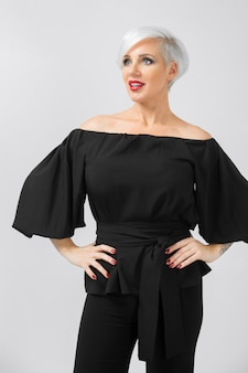 Dorosły piękny smilling modny bizneswoman w luźnych ubraniach na szaro