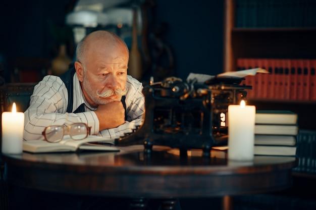 Dorosły pisarz pracuje na maszynie do pisania przy świetle świec
