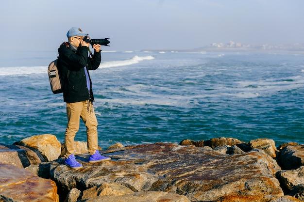 Dorosły podróżnik mężczyzna bierze fotografię piękny krajobraz od oceanu przylądka w portugalia z profesjonalną kamerą w pogodnym ranku.