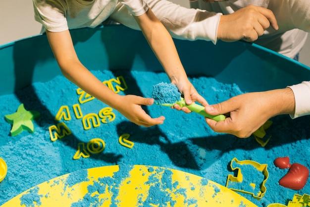 Dorosły pomaga dziecku w zabawie z piaskiem kinetycznym. terapia sztuką. łagodzenie stresu i napięcia. wrażenia dotykowe. kreatywność i przyjemność. rozwój umiejętności motorycznych. koncentracja i uwaga.