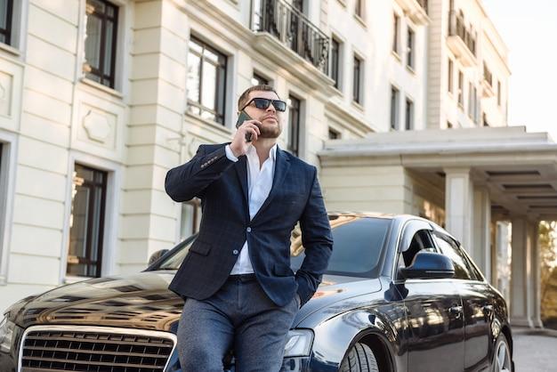 Dorosły poważny biznesmen mężczyzna w garniturze z telefonem w pobliżu samochodu na scenie ulicy miasta