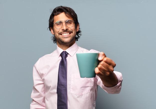Dorosły przystojny indyjski biznesmen z filiżanką kawy