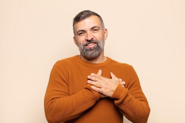 Dorosły przystojny mężczyzna czuje się romantyczny, szczęśliwy i zakochany, uśmiecha się radośnie i trzyma ręce blisko serca
