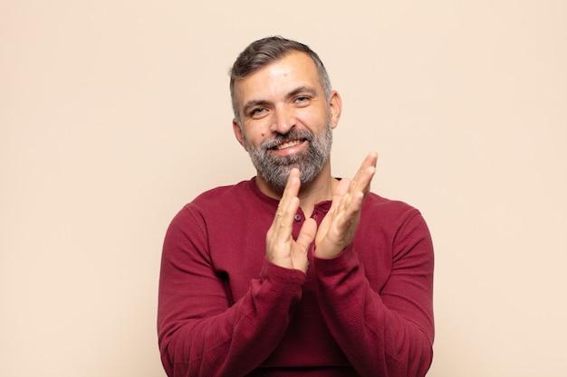 Dorosły przystojny mężczyzna czuje się szczęśliwy i odnosi sukcesy, uśmiechając się i klaszcząc w dłonie, gratulując z brawami