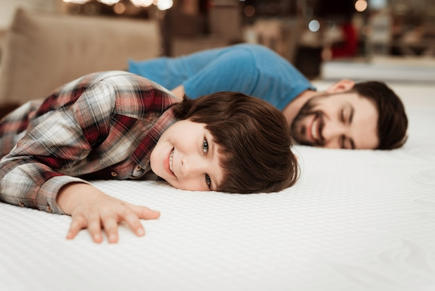 Dorosły przystojny mężczyzna i mały chłopiec na materacu