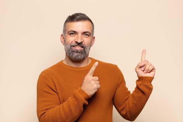 Dorosły przystojny mężczyzna uśmiecha się radośnie i wskazuje na bok i do góry obiema rękami, pokazując obiekt w przestrzeni kopii