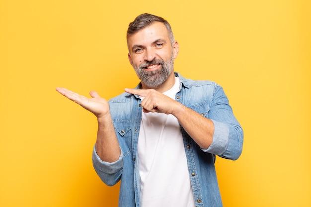 Dorosły przystojny mężczyzna uśmiecha się radośnie i wskazuje na kopiowanie miejsca na dłoni z boku, pokazując lub reklamując obiekt