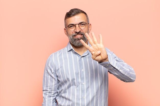 Dorosły przystojny mężczyzna uśmiechający się i wyglądający przyjaźnie, pokazujący cyfrę cztery lub czwartą z ręką do przodu, odliczając w dół