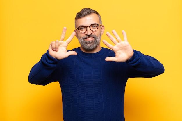 Dorosły przystojny mężczyzna uśmiechający się i wyglądający przyjaźnie, pokazujący cyfrę osiem lub ósmą z ręką do przodu, odliczając w dół