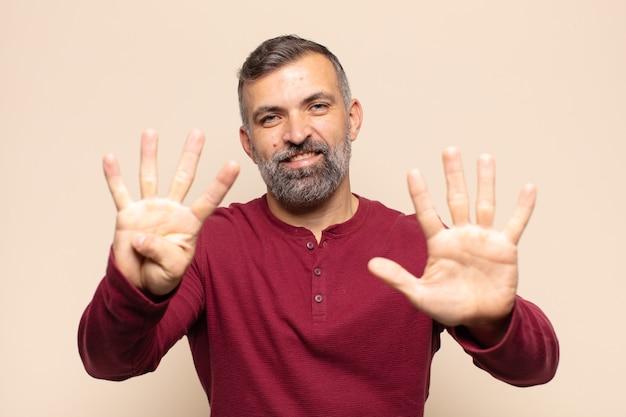 Dorosły przystojny mężczyzna uśmiechający się i wyglądający przyjaźnie, pokazujący numer dziewięć lub dziewiąty z ręką do przodu, odliczający w dół