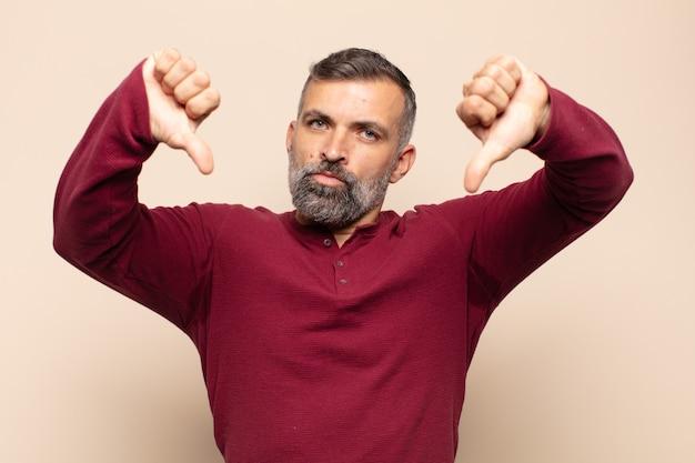 Dorosły przystojny mężczyzna wyglądający na smutnego, rozczarowanego lub złego, pokazujący kciuki w dół w niezgodzie, sfrustrowany