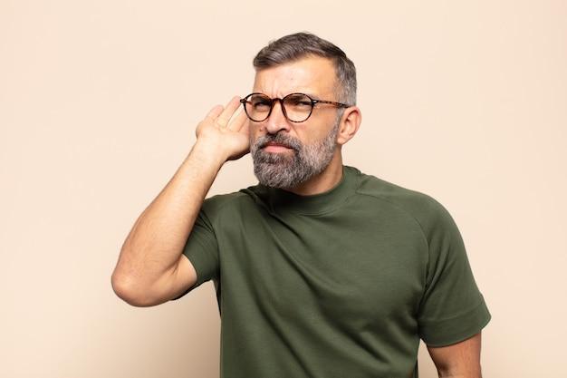 Dorosły przystojny mężczyzna wyglądający poważnie i zaciekawiony, słuchający, próbujący usłyszeć tajną rozmowę lub plotkę, podsłuchujący