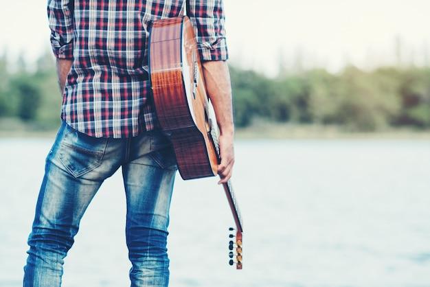 Dorosły przystojny muzyk grający na gitarze akustycznej