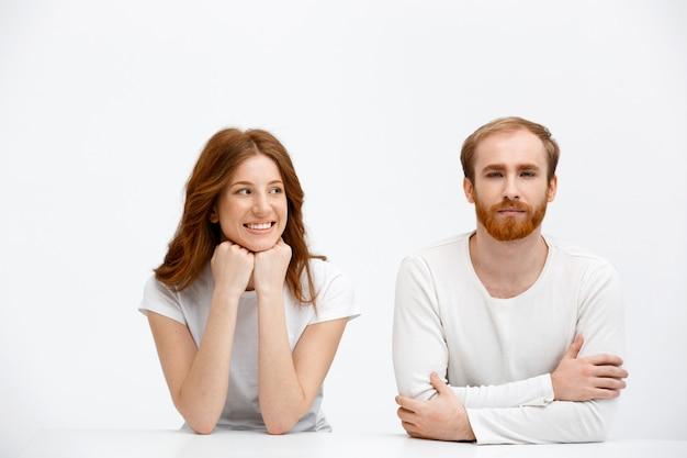 Dorosły rudy mężczyzna i kobieta siedzą przy biurku jak koledzy z klasy