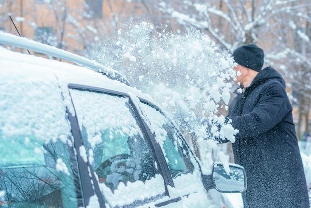 Dorosły samiec odśnieżający dach samochodu szczotką w sezonie zimowym
