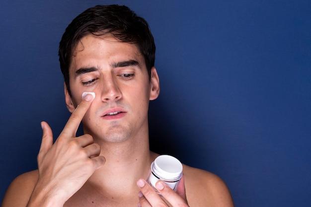 Dorosły samiec stosujący produkt do pielęgnacji skóry