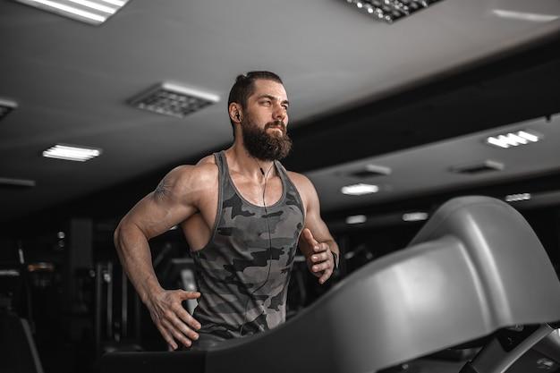 Dorosły silny brodaty mężczyzna na bieżni w siłowni.