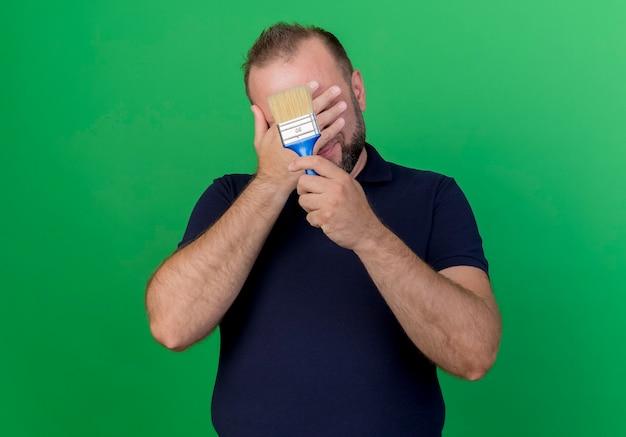 Dorosły słowiański mężczyzna trzyma pędzel obejmujący twarz ręką na białym tle na zielonej ścianie