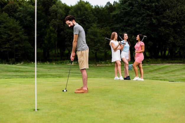 Dorosły sprawny człowiek trenuje golf na świeżym powietrzu