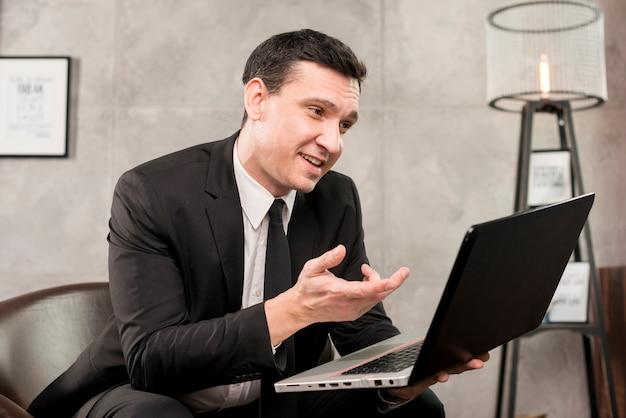 Dorosły uśmiechnięty biznesmen przegląda laptop w domu