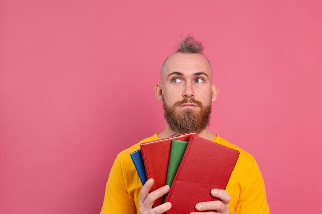 Dorosły uśmiechnięty facet z brodą przytula do siebie ulubione książki na różowym tle