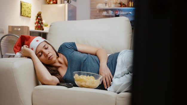 Dorosły w czapce świętego mikołaja śpi na kanapie w telewizji