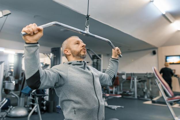 Dorosły wiek człowiek pracuje w siłowni szkolenia