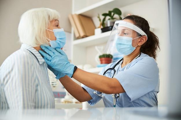 Dorosły wyciąga ręce obiema rękami i wywierając nacisk na szyję starej kobiety, aby wykryć jakiekolwiek problemy zdrowotne