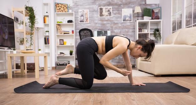 Dorosły z kobietą ze zdrowym stylem życia robi jogi na macie w salonie.