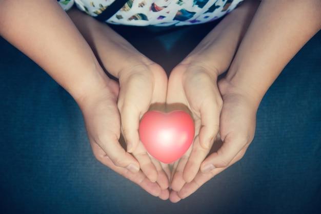 Dorosłych i dzieci posiadających czerwone serce piłkę w ręku