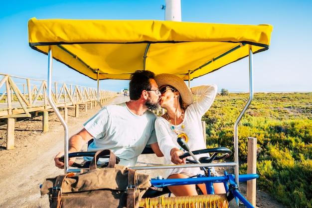 Dorosłych ludzi para zakochanych jeżdżących razem rzadki i zabawny kolorowy rower ein na świeżym powietrzu w naturze - szczęśliwy mężczyzna i kobieta całujący się z miłością - koncepcja relacji