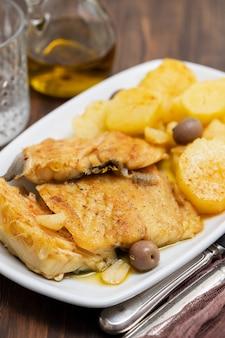 Dorsz ryba z smażonym ziemniakiem na białym naczyniu