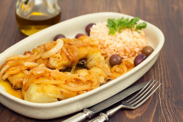 Dorsz smażony z gotowanym ryżem i oliwą z oliwek na talerzu