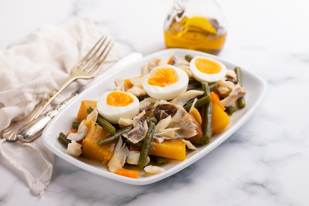 Dorsz z batatem i oliwkami na danie na ceramicznym tle
