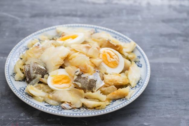 Dorsz z cebulą, jajkami i oliwą na talerzu