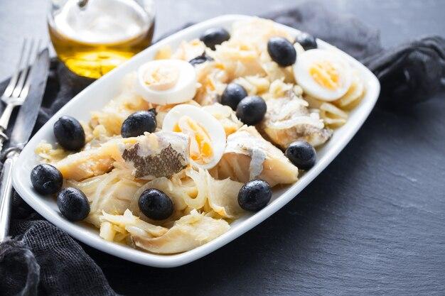 Dorsz z cebulą, oliwkami, jajkiem i oliwą na talerzu na ceramice