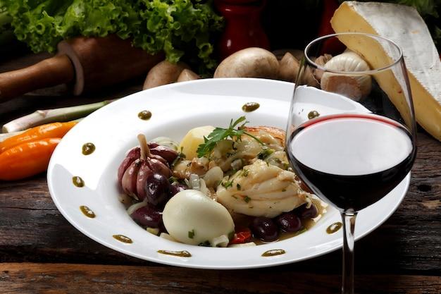 Dorsz z warzywami i kieliszkiem czerwonego wina